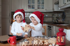 Two cute boys with santa hat, preparing cookies in the kitchen Royalty Free Stock Image
