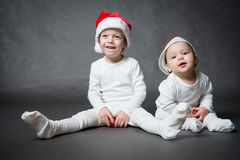 Two cute boys in Santa hats Royalty Free Stock Image