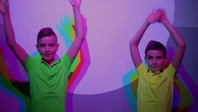 Two cute boys shows thumbs up, colorful shadows on the wall. Two boys plays with their colorful shadows on the wall. The museum of popular science and technology stock video footage
