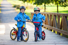 Two cute boys, siblings children, having fun on bikes in the par Stock Image