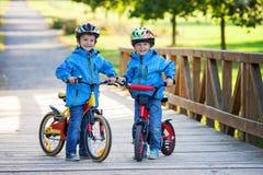 Two cute boys, siblings children, having fun on bikes in the par Stock Image