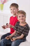 Two cute boys sitting on couch. Royalty Free Stock Images