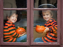 Two cute boys, sitting on a window with jack-o-lantern. Two cute boys, sitting on a window with pumpkins, smiling stock photos