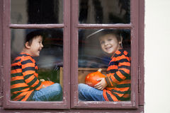 Two cute boys, sitting on a window with jack-o-lantern. Two cute boys, sitting on a window with pumpkins, smiling royalty free stock photography