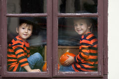 Two cute boys, sitting on a window with jack-o-lantern. Two cute boys, sitting on a window with pumpkins, smiling stock image