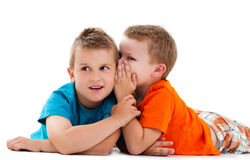 Two cute boys on white background sharing secrets Royalty Free Stock Photography