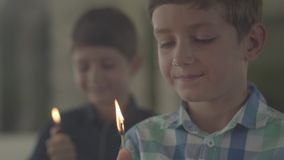 Two cute brothers with fire in the dark smoky room. One boy lit the lighter in the background another lit a match in the