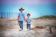 Two cute brothers, friends walking through the sandy desert field, playing cowboys, summer adventure royalty free stock image