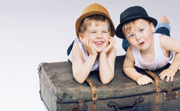 Two cute brothers lying on luggages Stock Images
