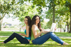Two cute brunette women sitting on a lawn smiling at camera. Using a laptop ans a tablet Royalty Free Stock Images