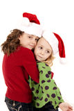 Two cute caucasian girls in santa hats hugging Stock Photography