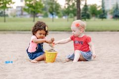 Two cute Caucasian and hispanic latin toddlers babies children sitting in sandbox playing with plastic colorful toys. Portrait of two cute Caucasian and hispanic royalty free stock photos