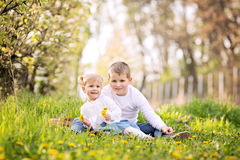 Two cute caucasian small kids, boy and girl, sitting in a grass Stock Photography