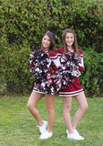 Two Cute Cheerleaders. Two very cute teen aged cheerleaders posing outdoors on a green lawn Royalty Free Stock Photography