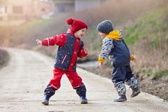 Two cute children, boy brothers, playing together in the park, r Royalty Free Stock Image
