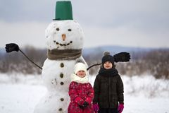 Two cute children, boy and girl, standing in front of smiling snowman in bucket hat, scarf and gloves on snowy winter landscape an royalty free stock images
