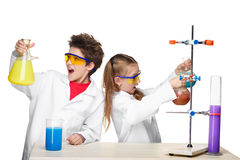 Two cute children at chemistry lesson making. Experiments isolated on white background Stock Photography