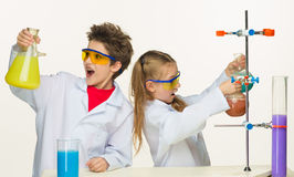 Two cute children at chemistry lesson making. Experiments on white background Royalty Free Stock Photography