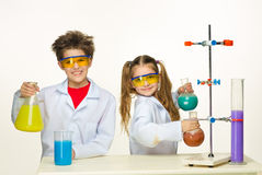 Two cute children at chemistry lesson making royalty free stock images