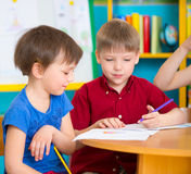 Two cute children drawing at kindergarten Stock Images