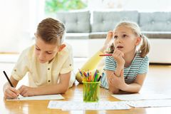 Two cute children draws with colorful pencils at home Royalty Free Stock Image