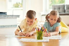 Two cute children draws with colorful pencils at home Stock Photos