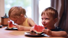 Two cute children girl and boy eating a watermelon. Brother and sister sitting at the table, have a meal together. stock video