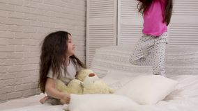 Two cute children girls playing in the bedroom. stock video