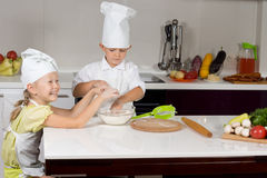 Two cute children making homemade pizza Royalty Free Stock Photos