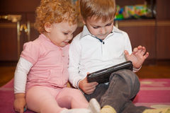 Two cute children playing with tablet Royalty Free Stock Photos