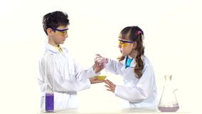 Two cute children in protactive glasses and. Two cute children, boy and girl with ponytails, in protactive glasses and white  uniform making chemical experiments stock video