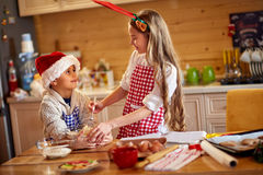 Two cute children with Santa hat, preparing xmas cookies Stock Photos