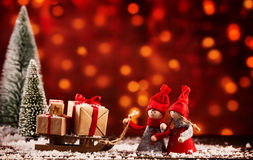Two cute Christmas figures with a sled of gifts. Two cute little Christmas figures with a sled full of gifts in a snowy winter landscape with colorful bokeh of Royalty Free Stock Photography