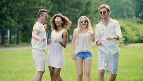 Two cute couples hanging out at open-air festival, dancing to music, having fun. Stock footage stock footage