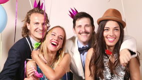Two cute couples having fun in party photo booth