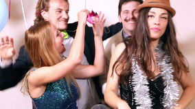 Two cute couples having fun in party photo booth stock video