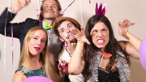 Two cute couples making funny faces in party photo booth. Two cute young couples making funny faces in party photo booth stock footage