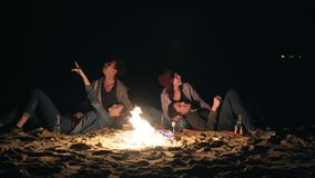 Two cute couples sitting by the bonfire late at night and looking at the stars.  stock footage