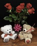 Two cute cuddly teddy bears with red roses in vase and pink bow on wooden table on dark background stock photography