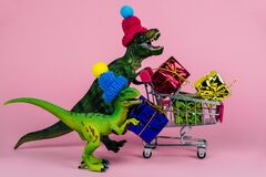 cute dinosaurs in knitted hats with shopping trolley full of present boxes, sale concept