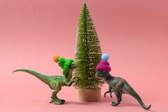 cute dinosaurs wearing knitted hats near christmas tree on a soft pink background
