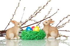 Two cute Easter bunnies near Easter eggs nest. Two cute Easter bunnies sitting beside an Easter nest. In the nest is a yellow, a red and blue Easter egg. In Stock Photography