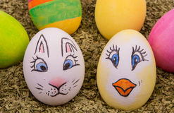 Two cute eggs with painted Easter bunny and chicken. Two eggs with motifs of an Easter bunny and chicken with multi colored eggs in the background Royalty Free Stock Photos
