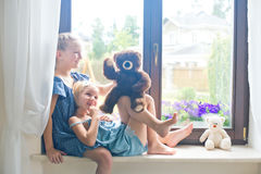 Two cute european toddler girls playing toys near window at home Royalty Free Stock Photography