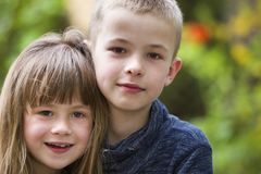Two cute fair-haired children siblings, young boy brother and sister girl outdoors on bright sunny green bokeh background. Family. Relation, friendship and love stock photos