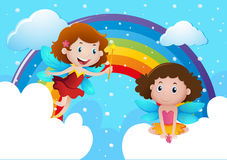 Two cute fairies flying over the rainbow Stock Images