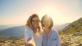 Two cute female friends make selfie. Two best friends make selfie photograph on actioncamera or smartphone, beautiful young millennial hipsters smile and laugh stock footage