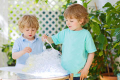 Two cute friend boys making experiment with colorful bubbles. Two adorable friend boys making experiment with colorful soap bubbles and water, outdoors stock photography
