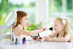 Two cute funny sisters applying make-up on sunny summer day at home. Adorable girls playing with their mommy`s cosmetic accessories Stock Photo