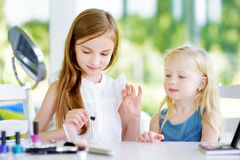 Two cute funny sisters applying make-up on sunny summer day at home. Adorable girls playing with their mommy`s cosmetic accessories Royalty Free Stock Image